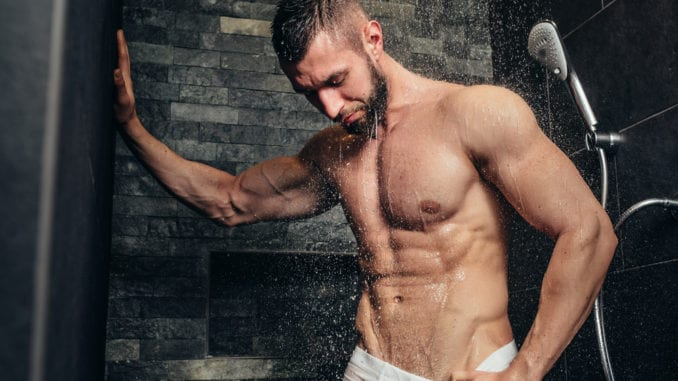 shirtless, muscular man taking a shower in modern bathroom
