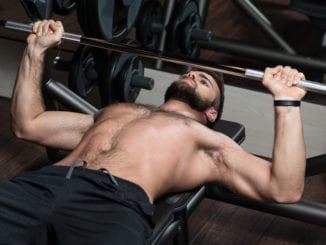 man lifting weights gym