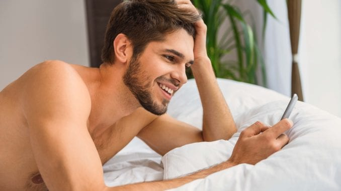 attractive man cellphone in bed
