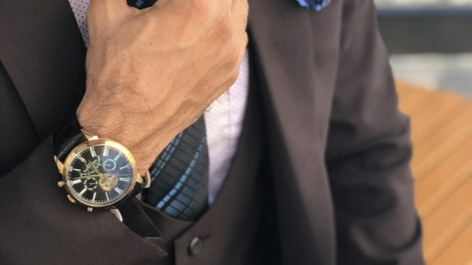 man adjusting tie wristwatch