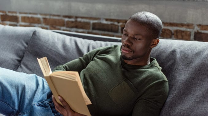attractive black man reading book on couch