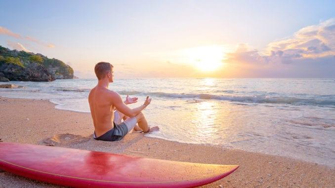 man meditating beach