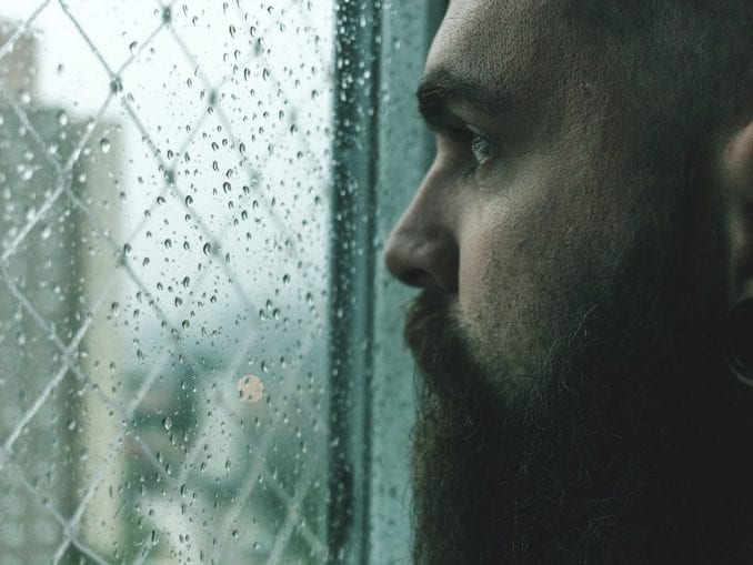 man looking out window afraid